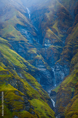 Water falling over rugged rocks in a lush green Himalayan landscape at Annapurna Base camp, Nepal.