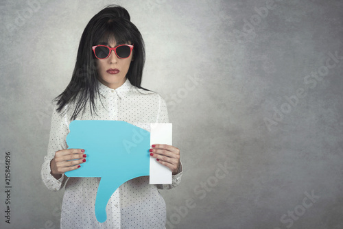 Young Woman holding a dislike icon on gray background Canvas-taulu