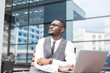 african businessman in suit and glasses is sitting at a table with a Laptop, a cup of coffee against a background of glass buildings