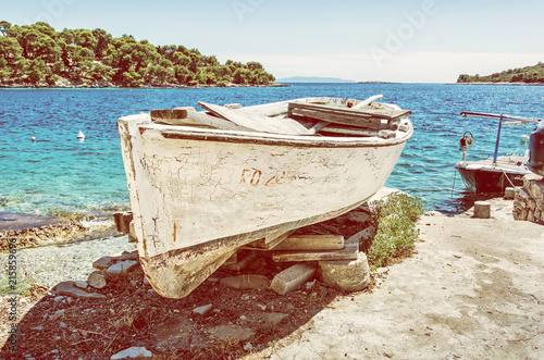 Fotografia Old fishing boat with cracked white paint, Solta, yellow filter