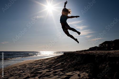 Girl jumping off sand dune with bright sun silhouette