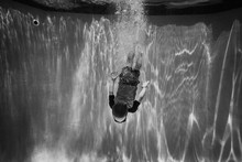 Boy Diving Underwater With Bubbles And Light