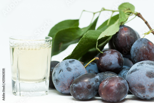 romanian plum brandy known as tuica or tzuica and heap of ripe plums on white