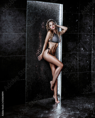 Keuken foto achterwand Akt Beautiful sexy blonde girl with wet hair. Posing in a swimsuit in the shower under the drops of water