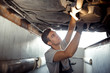 A qualified automechanic is conducting an examination of a lifte
