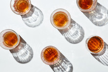 Tumblers With Golden Alcoholic Drinks On White Background.