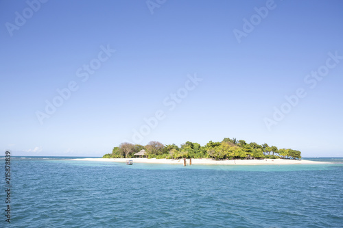 Island amidst sea against clear blue sky