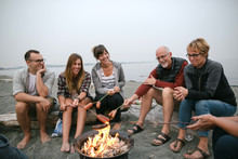 Multi Generational Family Hanging Out Together Around Fire On The Beach