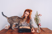 Woman Trying To Work While Her Cat Is Playing Whit The Typewriter
