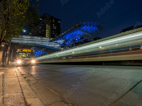 A transit bus is passed by a train at a station at night.