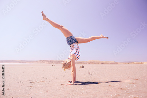 Fotografia  Girl gymnast on the background of the desert, walking on his hands