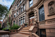 a row of brownstone buildings and stoops in an iconic neighborhood of Manhattan, New York City.