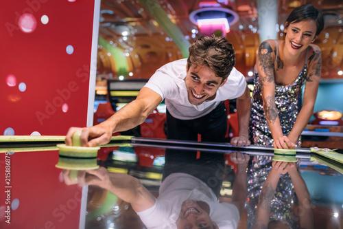 Canvastavla Couple playing air hockey game at a gaming arcade