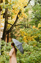 Young Woman With A Black Umbrella In Autumn Scene. Back View.