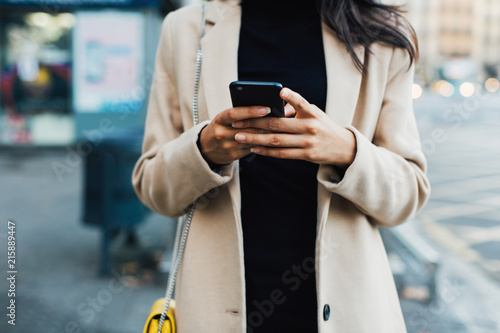 Stylish woman in the city using smartphone.