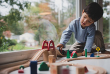 Little Kid Playing With Train Set