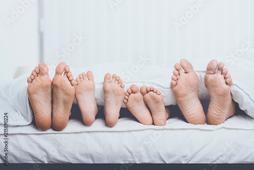 Fotografie, Obraz  Close up Family in Bed under Cover Showing Feet