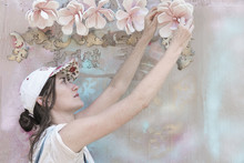 Woman Decorating A Painted Wall With Flowers