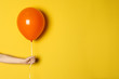 canvas print picture - Woman holding orange balloon on color background