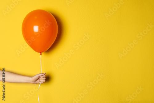 Fototapeta Woman holding orange balloon on color background obraz