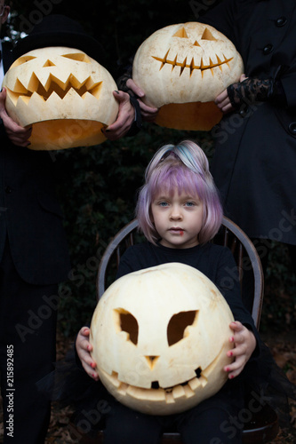 A little girl with purple hair holds a carved pumpkin head.