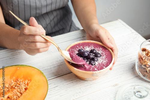 Valokuva  Woman eating tasty acai smoothie at table, closeup