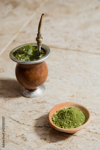 Fotografie, Obraz  Yerba mate tea in a pottery bowl and a drinking cup with bombilla over a marble surface
