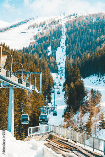 March 20, 2018. Austria. Ski lifts and cable cars going up the mountain bringing snowboarders to ski slopes. Ski resort.