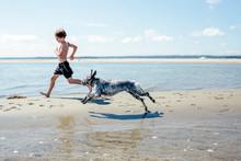 Boy Runs On The Beach With His...