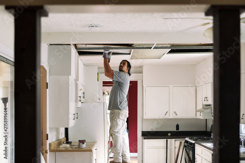 Kitchen Man Removing Drop Ceiling Tiles