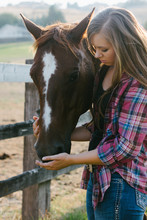 Teenage Girl Fondly Holding Muzzle Of Her Horse