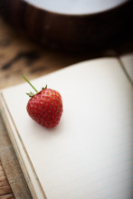 Single Strawberry On A Blank Page Of A Notebook.