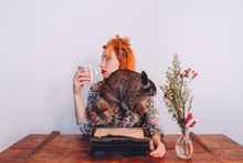 Woman Having A Coffee While Her Cat Is Playing With The Typewriter