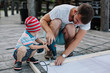Father and son working together with electric screwdriver outdoors