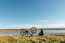 A Woman Resting And Using Her Mobile Phone Next Her Mountain Bike In Front Of A Lake At A Wind Farm In Scotland