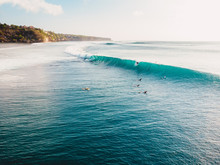 Aerial View With Surfers And Barrel Blue Wave In Ocean