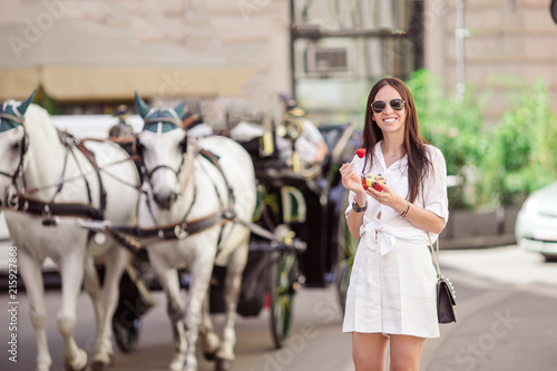 Tourist girl enjoying vacation in Vienna and looking at the beautiful horses in Wallpaper Mural