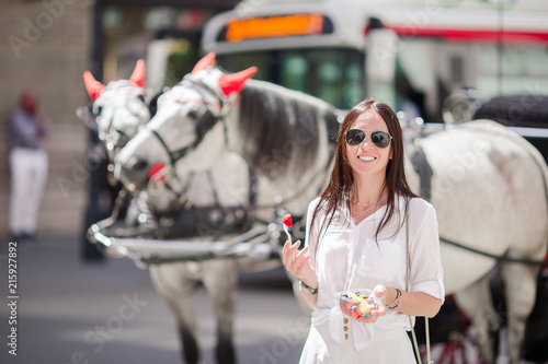 Tourist girl enjoying vacation in Vienna and looking at the beautiful horses in Canvas Print