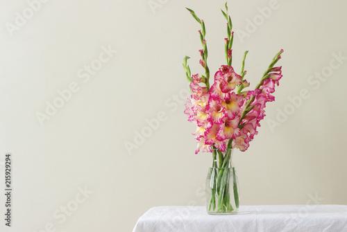 A bouquet of multicolored gladioli in a glass vase on a light background Billede på lærred