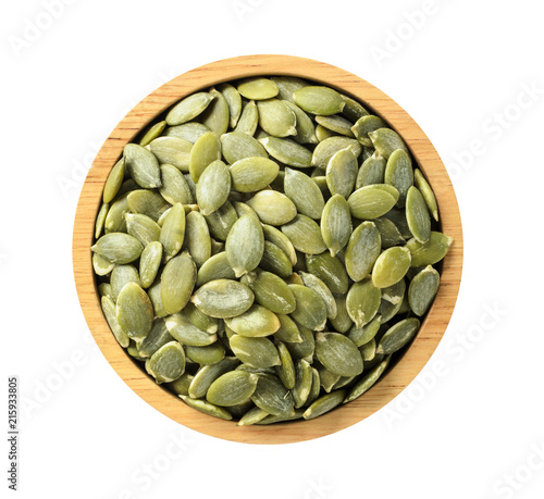 Dry pumpkin seeds in wooden bowl on white background