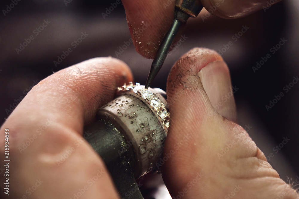 Fototapeta Close up of the hands of a goldsmith while he is making a diamond ring. Concept: jewelry, gold, fashion