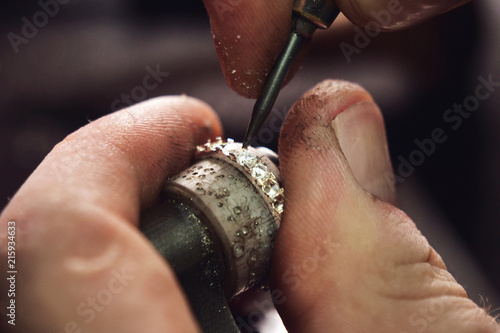 Fotografia  Close up of the hands of a goldsmith while he is making a diamond ring