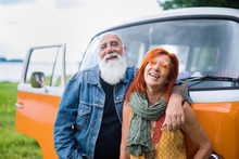 An Old Hipster Couple Posing In Front Of Their Vintage Van