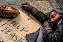 Homeless Male Getting To Sleep On Floor In Public Path Way With Old Hat In Front For Money Donation