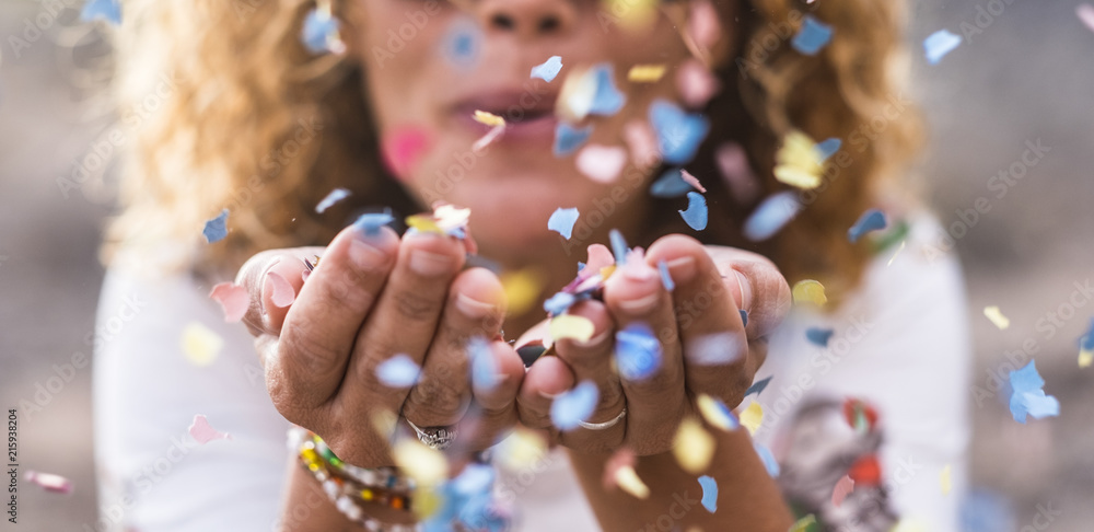 Fototapeta beautiful defocused woman blow confetti from hands. celebration and event concept. happiness and coloured image. movement and happiness having fun