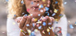 canvas print picture - beautiful defocused woman blow confetti from hands. celebration and event concept. happiness and coloured image. movement and happiness having fun