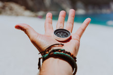 Open Palm With Stretched Fingers Holding Black Metal Compass Against White Sandy Beach. Find Your Way Or Goal Concept. Point Of View Pov