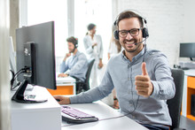 Happy Male Customer Service Operator Showing Thumb Up In Office.