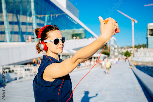 Fotografía  Young hipster woman traveler walking in Oslo city on quay, listening to music with red headphones, street style, urban Oslo Opera House background, holding smart phone, taking selfie photo