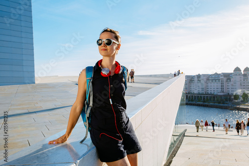 Photo  Young hipster woman traveler in sunglasses walking in Oslo city summer sunny day with red headphones, backpack, street style, Opera House urban background, , happy, smiling